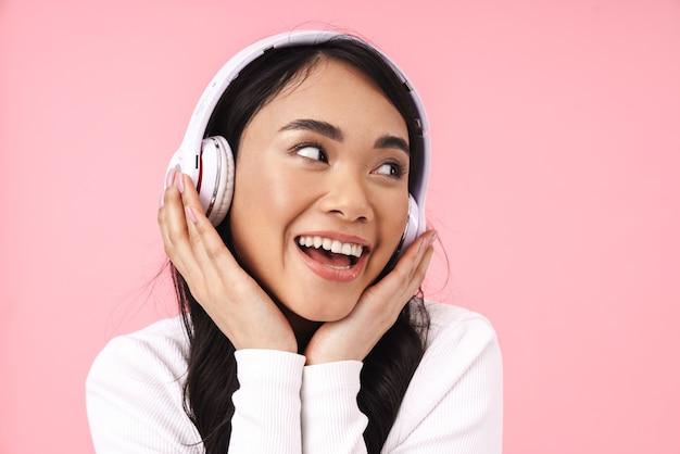 Веселая довольно молодая азиатская женщина слушает музыку с изолированными беспроводными наушниками