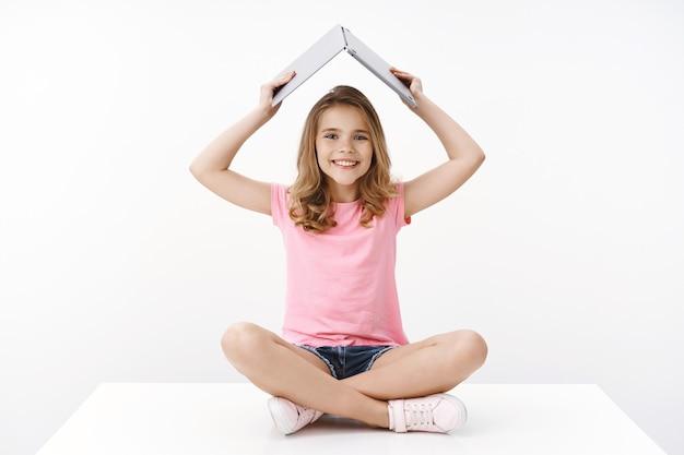 Studente bambino biondo piuttosto giovane allegro, seduto divertito e felice sul pavimento gambe incrociate, alza il laptop aperto sotto la testa, sorride ampiamente, entusiasta di studiare l'e-learning vuole diventare programmatore