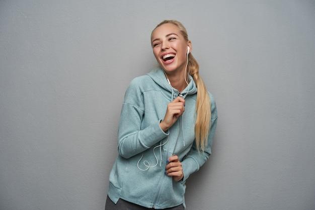 밝은 회색 배경 위에 서있는 동안 이어폰과 스포티 한 옷을 입고 캐주얼 헤어 스타일을 제쳐두고 행복하게 웃고있는 쾌활한 꽤 젊은 금발 여성