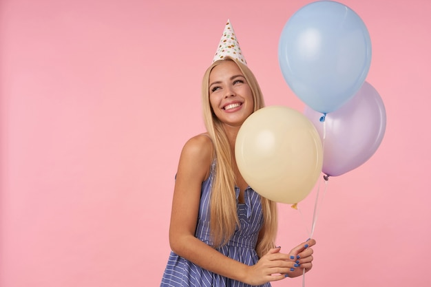 Веселая симпатичная молодая блондинка с длинными волосами, держащая разноцветные воздушные шары, стоя на розовом фоне в праздничной одежде, глядя в сторону с широкой искренней улыбкой