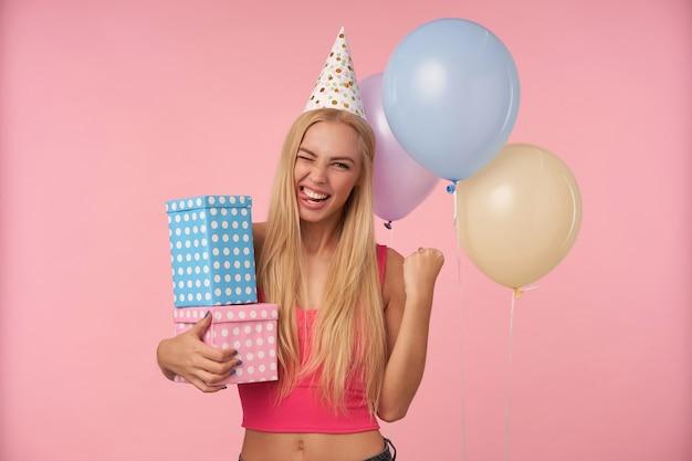 Веселая симпатичная молодая блондинка женщина радуется красивой вечеринке вместе с друзьями, пребывая в приподнятом настроении и счастливо поднимая кулак, изолирована на розовом фоне и кучей разноцветных гелиевых шаров