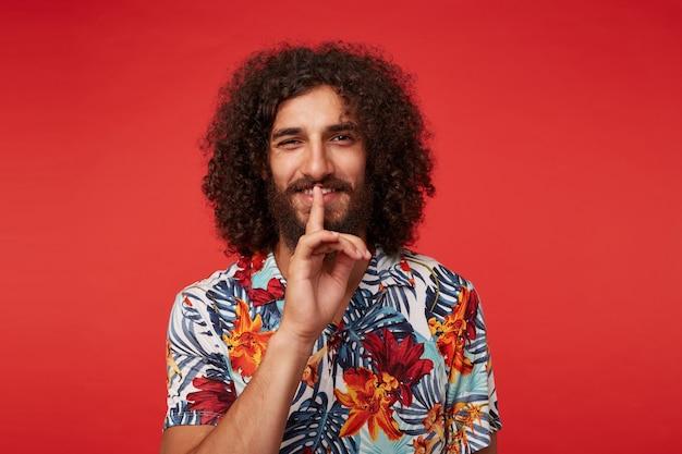 Веселый симпатичный молодой брюнет кудрявый мужчина с бородой поднимает указательный палец в жесте тишины, положительно смотрит в камеру с приятной улыбкой, изолированный на красном фоне в повседневной одежде