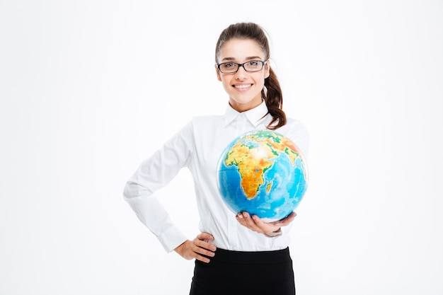 Cheerful pretty young businesswoman smiling and holding globe over white wall