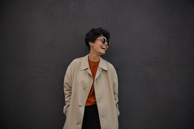 Cheerful pretty young curly woman with casual hairstyle looking aside happily and laughing joyfully, keeping hands in pockets of her stylish beige trench