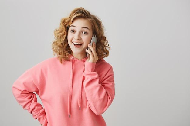 Веселая симпатичная молодая девушка разговаривает по телефону и улыбается