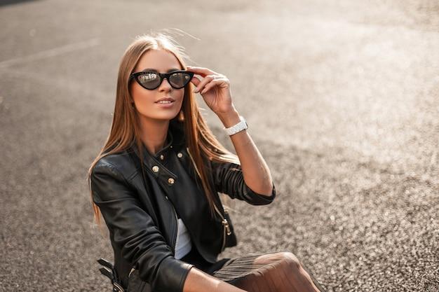 우아한 검은 치마에 세련된 가죽 재킷에 쾌활한 예쁜 젊은 hipster 여자는 화창한가 날에 아스팔트에 쉬고 있습니다. 귀여운 미소로 행복한 소녀가 유행 선글라스를 곧게 만듭니다.