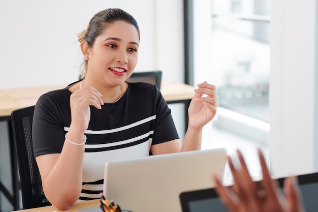 Cheerful pretty young indian businesswoman sitting at office desk and talking to colleague about project they are working on