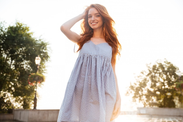 Cheerful pretty young redhead woman with long hair posing