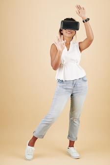 バーチャルリアリティメガネでビデオゲームをプレイする陽気なかなり若い笑顔の女性