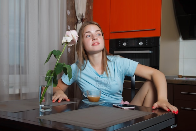 쾌활하고 예쁜 젊은 10대 여성이 식탁에서 일어나 예상치 못한 것을 보면 시선을 돌립니다. 귀여운 여성 쇼 감정 테이블에 외로운 장미 옆에 누군가를 기다리고 있습니다. 저작권 공간
