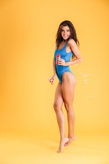 Cheerful pretty young woman in blue swim wear having fun with soap bubbles isolated on a orange wall