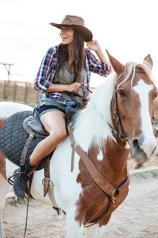 Cheerful pretty young woman cowgirl sitting and riding horse in village