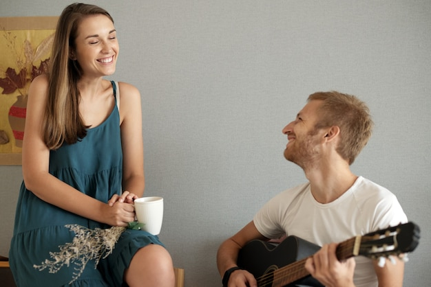 Веселая симпатичная молодая женщина наслаждается красивой песней своего красивого парня
