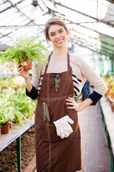 Веселая симпатичная молодая женщина-садовник в коричневом фартуке стоит в оранжерее и держит папоротник в горшке