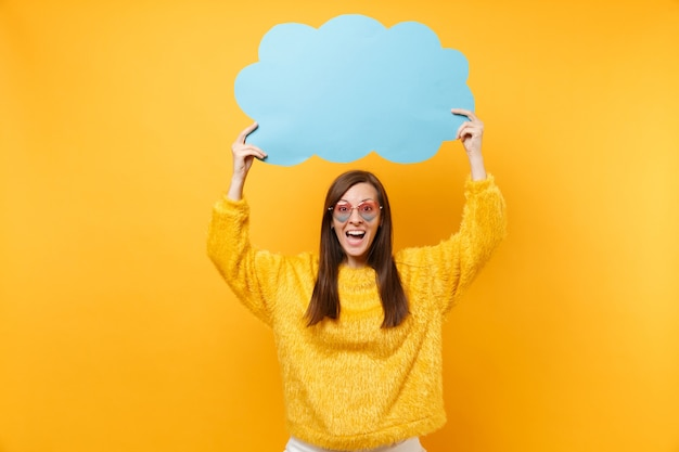 Cheerful pretty young woman in heart eyeglasses holding empty blank blue say cloud, speech bubble isolated on bright yellow background. people sincere emotions, lifestyle concept. advertising area.