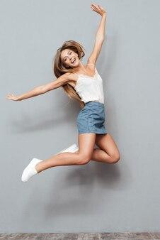 쾌활 한 예쁜 젊은 여자에 고립 된 회색 배경 점프