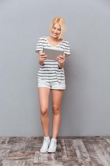 Веселая симпатичная молодая женщина, стоящая и использующая планшет