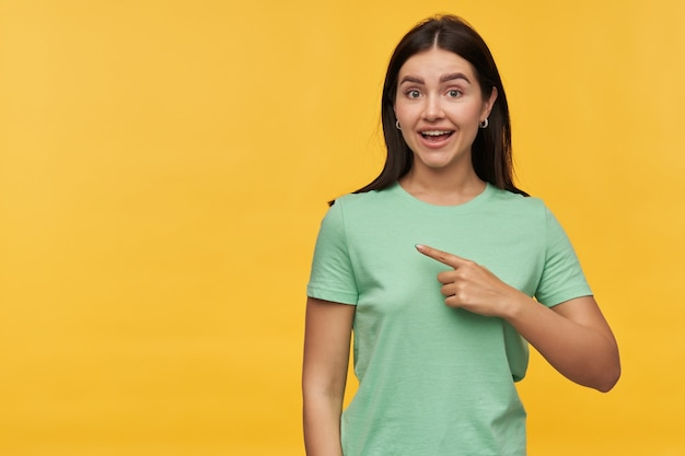 Cheerful pretty young woman with dark hair in mint tshirt  and pointing away to the side at copyspace isolated over yellow wall