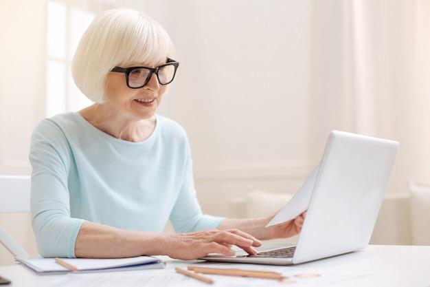 컴퓨터에 입력하는 동안 읽고있는 기사에 대한 리뷰를 작성하는 쾌활한 생산적인 야심 찬 여성