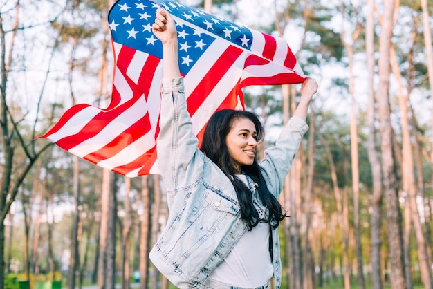 Cheerful proud female raising american flag