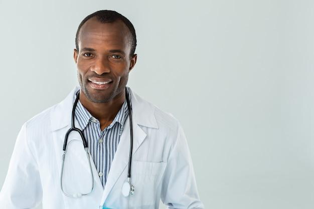 흰 벽에 서있는 동안 웃 고 쾌활 한 정신과 의사