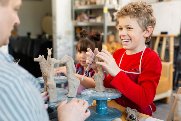Cheerful pupil smiling broadly while modeling clay figures