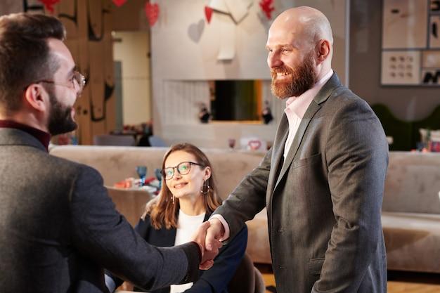 Веселый рыжебородый бизнесмен пожимает руку новому деловому партнеру после переговоров в кафе