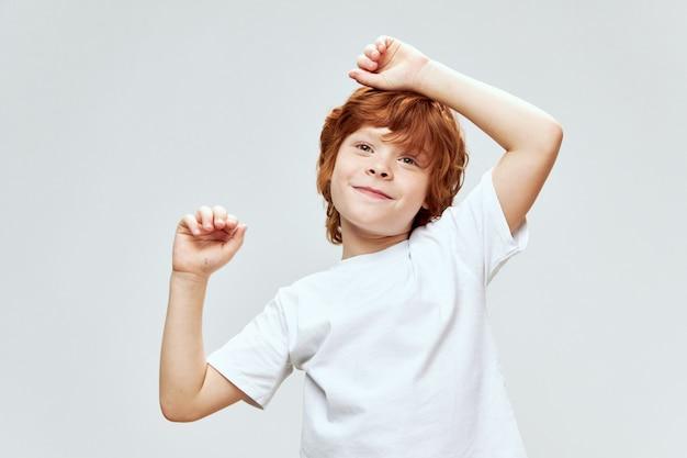Веселый рыжий мальчик держится за голову белую футболку
