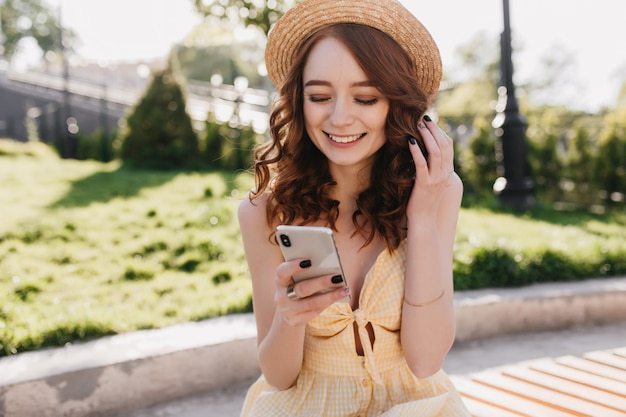 Cheerful red-haired girl in cute hat read messages with happy smile. outdoor photo of lovable ginger woman in yellow dress relaxing in park in morning.