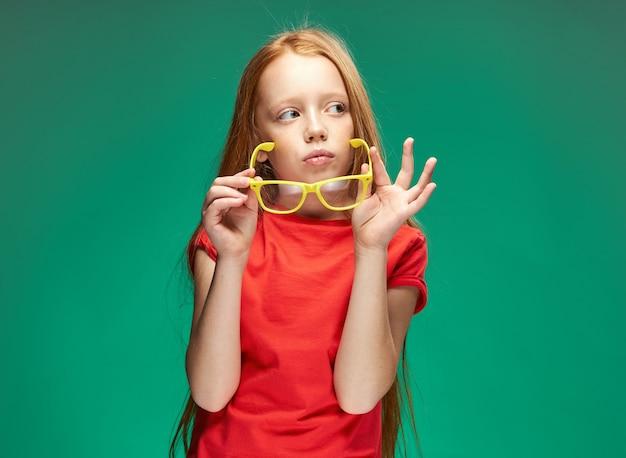 Веселая рыжеволосая девушка держит очки в руках, изучая школьный зеленый фон. фото высокого качества