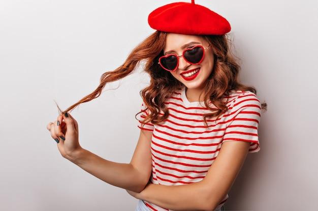 Allegra ragazza dai capelli rossi che gioca i suoi capelli ricci. estatica bella donna in berretto.