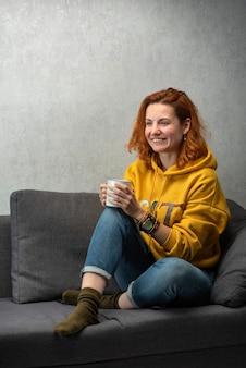 Веселая рыжеволосая девушка с чашкой в руках на диване