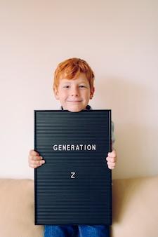Веселый рыжий маленький мальчик держит доску с текстом «поколение z»