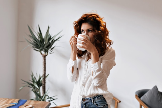 Cheerful red-haired woman drinking coffee enjoying leisure at cafeteria and looking at window during break