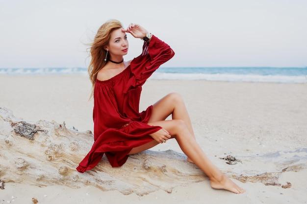 밝은 빨강 머리 소녀 해변에서 포즈. 하얀 모래에 앉아. 바람이 센 머리카락. 유행 복장. 라이프 스타일 초상화. 여행 분위기. 오션 코스트.