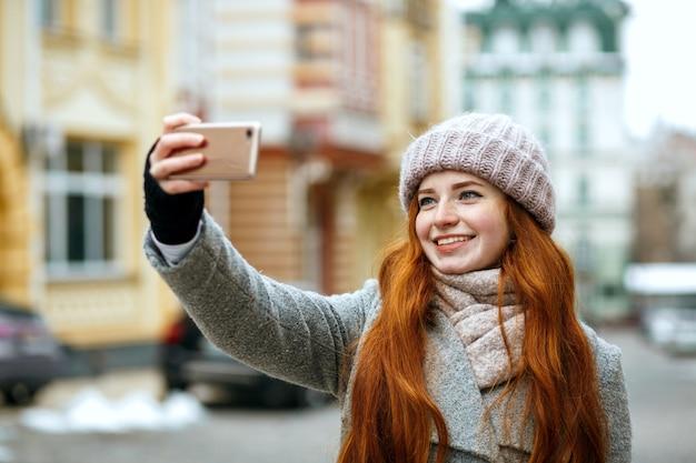 彼女の携帯電話で自分撮りをしている冬のアパレルの陽気な赤い頭のモデル。テキスト用のスペース