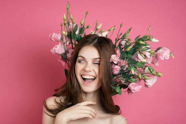 花のピンクの背景の魅力のドレスブーケで陽気なredhaired女性