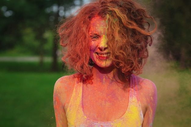 공원에서 다채로운 건조 holi 페인트로 덮여 포즈 쾌활한 redhaired 여자