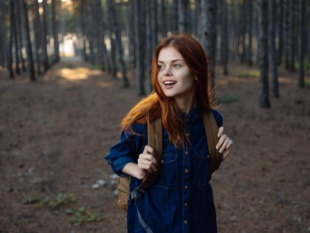 森の旅でバックパックを背負って陽気な赤毛の女性