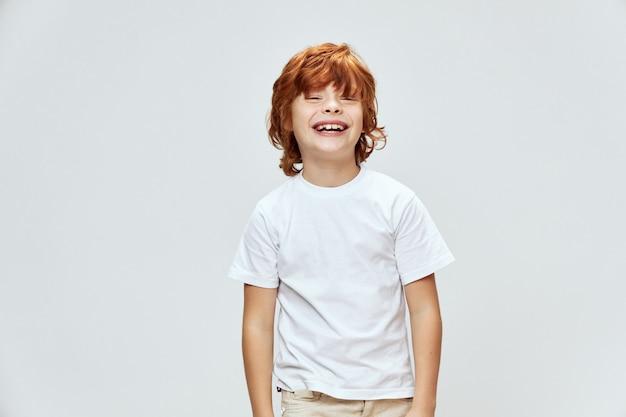 Веселый рыжий мальчик позирует