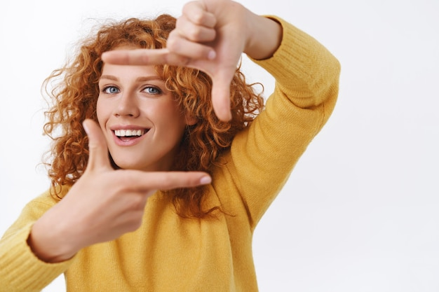 Cheerful redhead curly woman imaging she hold camera, making frame hands and smiling looking through, search perspective or right angle to take awesome shot, photographing, white wall