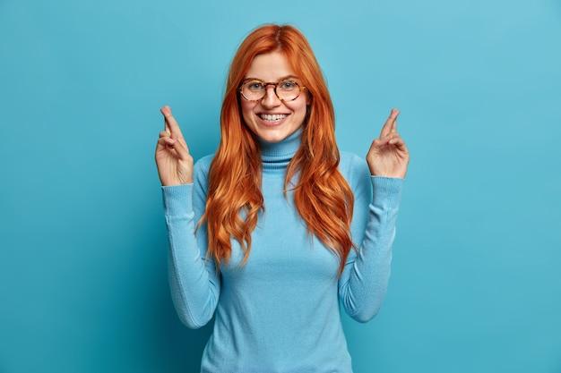 쾌활한 빨간 머리 유럽 여성의 미소는 기꺼이 손가락을 교차시켜 캐주얼 터틀넥을 입은 긍정적 인 결과를 얻기를 희망합니다.