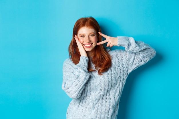 쾌활한 빨간 머리 여성 모델은 파란 배경 위에 서서 미소를 지으며 평화의 신호를 보내고 좋은 분위기를 자아냅니다.
