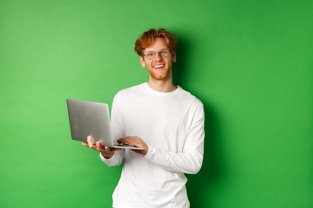 녹색 배경 위에 서있는 동안 노트북에서 작동하는 카메라에 웃 고 안경에 쾌활 한 빨간 머리 프리랜서.