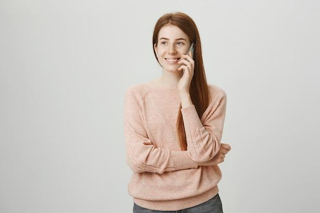 携帯電話で話している陽気な赤毛の女の子笑顔