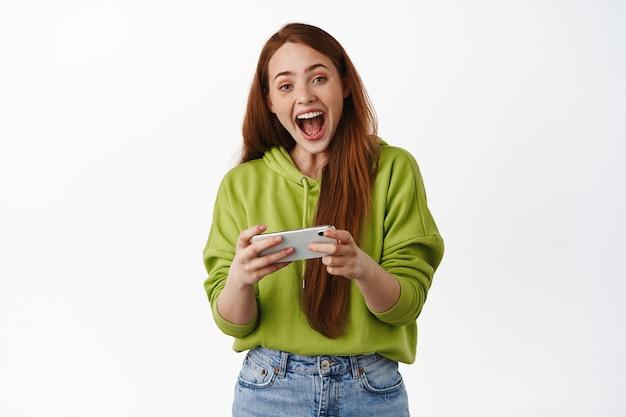 スマートフォンを持ってモバイルビデオゲームをプレイし、笑って笑って、楽しんで、白地にカジュアルな服を着て立っている陽気な赤毛の女の子