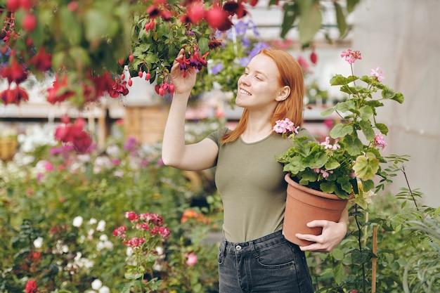 Веселая рыжая девушка в футболке цвета хаки трогает красные цветы на ветке и держит растение в горшке, наслаждаясь работой в саду