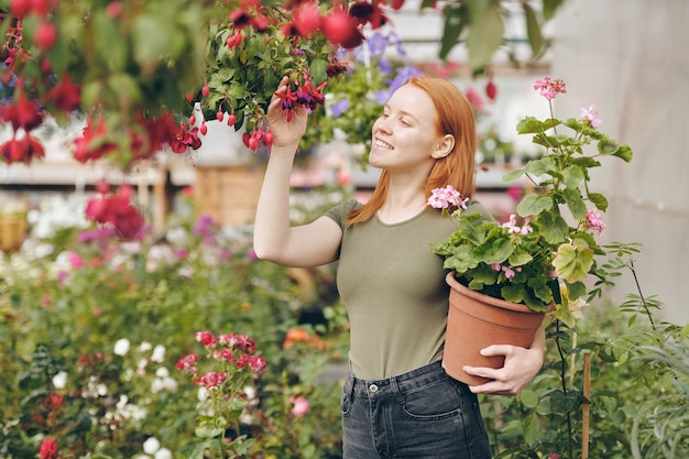 Cheerful redhead girl in khaki tshirt touching red flowers on twig and holding potted plant while enjoying work in garden