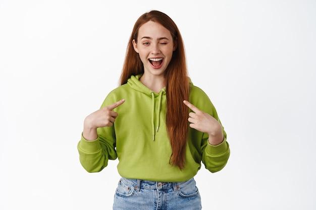 쾌활한 빨간 머리 소녀는 자신을 가리키며 윙크를 하고 행복하게 웃고 있으며 흰색 캐주얼 옷을 입고 서 있다고 말합니다.
