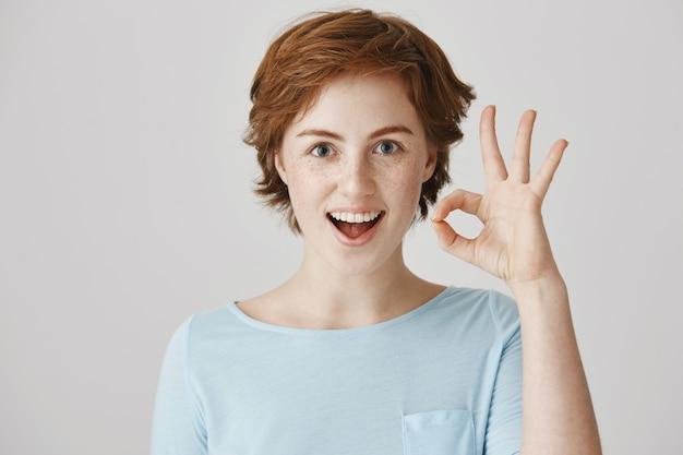 白い壁にポーズをとって陽気な赤毛の女の子